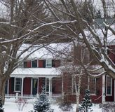 Santa& x27;s red farm house covered with snow surrounded by snow covered branches and trees. White picket fence, porch, grey winters day, 2 royalty free stock photography