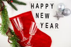 Santa`s red stocking on a white background together with a toy in the form of a star and a ball, champagne glasses. Happy new yea