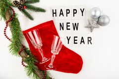 Santa\'s red stocking on a white background together with a toy in the form of a star and a ball, champagne glasses. Happy new yea