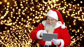 Santa`s talking with someone through the gadget. stock footage