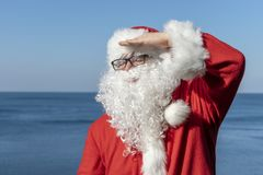 Santa looks into the distance, standing on the ocean. Traditional red outfit and relaxing on the beach. Santa`s vacation at sea. Relaxing on the beach royalty free stock images