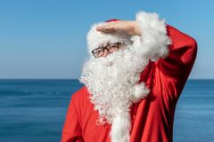 Santa looks into the distance, standing on the ocean. Traditional red outfit and relaxing on the beach. Santa`s vacation at sea. Relaxing on the beach royalty free stock photography