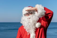 Santa looks into the distance, standing on the ocean. Traditional red outfit and relaxing on the beach. Santa`s vacation at sea. Relaxing on the beach royalty free stock photos