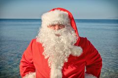 Santa`s vacation at sea. Traditional red outfit and relaxing on the beach stock photo