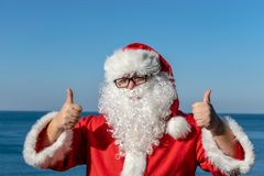 Santa`s vacation at sea. Traditional red outfit and relaxing on the beach. Santa`s vacation at sea. Relaxing on the beach stock images