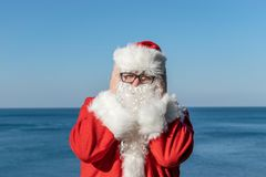 Santa`s vacation at sea. Traditional red outfit and relaxing on the beach. Santa`s vacation at sea. Relaxing on the beach royalty free stock photo