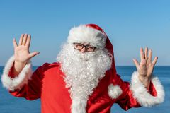 Santa`s vacation at sea. Traditional red outfit and relaxing on the beach. Santa`s vacation at sea. Relaxing on the beach royalty free stock image