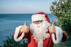 Santa`s vacation at sea. Traditional red outfit and and rest at the resort royalty free stock photos