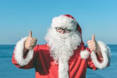 Santa`s vacation at sea. Traditional red outfit and relaxing on the beach. Santa`s vacation at sea. Relaxing on the beach stock photography