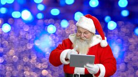Santa`s wishing merry Christmas through the tablet. stock video footage
