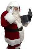 Santa's Workload. Santa Claus (isolated on white) reviewing his laptop while on his cell phone Stock Image