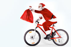 Santa with sack. Photo of happy Santa Claus on bike with red sack in stretched arm Royalty Free Stock Photos
