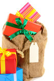 Santa sack or mail bag full with pile of Christmas gifts isolated on white background Royalty Free Stock Photography