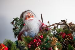 Santa. Claus figure wearing glasses amongst the Christmas decorations. Shallow focus Stock Images