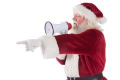 Santa se dirige à quelque chose et utilise un mégaphone Photographie stock libre de droits