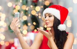 Женщина в шляпе santa принимая selfie smartphone Стоковые Изображения RF