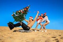 Santa sexy che tirano Santa alla spiaggia Fotografie Stock Libere da Diritti