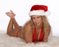 Santa sexy dans le bikini rouge se trouvant sur l'estomac avec des chevilles a croisé Image libre de droits