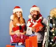 Santa and girl with pink gift bag. Christmas gifts. And love concept. Couple in love with red and blue presents near fir tree. Man with beard and women with stock image