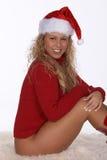 Santa sexy in maglione rosso e caricamenti del sistema messi sulla coperta della pelliccia Fotografia Stock Libera da Diritti
