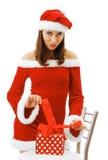 Santa 'sexy' que amarra acima de um presente de Natal Foto de Stock