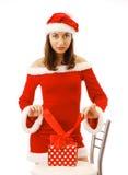 Santa 'sexy' que amarra acima de um presente de Natal Foto de Stock Royalty Free