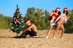 Santa 'sexy' que puxam Santa na praia Fotos de Stock Royalty Free