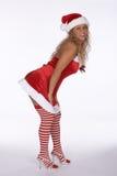 Santa sexy in vestito rosso con il piegamento messo a nudo delle calze Fotografia Stock Libera da Diritti