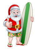 Santa in Shorts Holding Surfboard Royalty Free Stock Photo