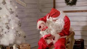 Santa siedzi w krześle i próbuje faszerować zabawkę jako prezent Zdjęcia Stock