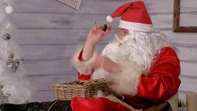 Santa siedzi w krześle i rzuca zabawki Zdjęcie Stock