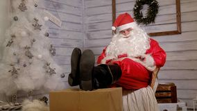 Santa siedzi w krześle stawia jego cieki na prezencie Fotografia Stock