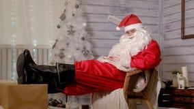 Santa siedzi w krześle stawia jego cieki na prezencie Zdjęcia Royalty Free