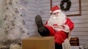 Santa siedzi w krześle stawia jego cieki na prezencie Zdjęcia Stock