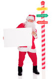 Santa with a Sign. Full-length image of Santa holding a blank sign (for your text) by a North Pole striped directional pole Stock Photography