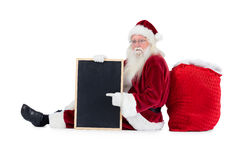 Santa sits leaned on his bag with a board Royalty Free Stock Images