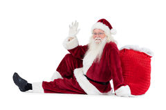Santa sits leaned on his bag and waves Royalty Free Stock Images