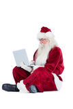 Santa sits and uses a laptop Stock Photo