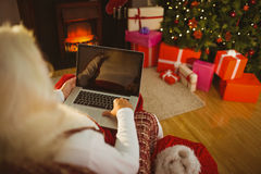 Santa sitting on the armchair and typing on laptop Royalty Free Stock Images