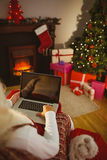 Santa sitting on the armchair and typing on laptop Royalty Free Stock Photos