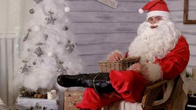 Santa is sitting in a chair and throwing toys. 4k Stock Photography