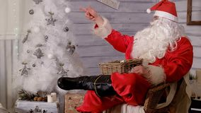 Santa is sitting in a chair and throwing toys. 4k Royalty Free Stock Photography
