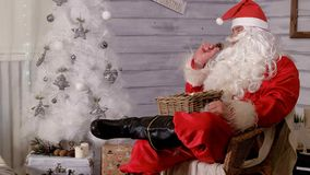 Santa is sitting in a chair and throwing toys. 4k Stock Image