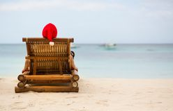Santa sitting on chaise longue on beach. Santa sitting on chaise longue on white sand beach stock photos