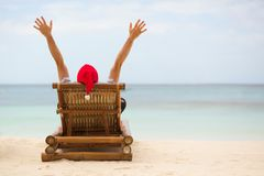 Santa sitting on chaise longue on beach Stock Images