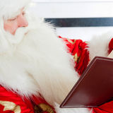 Santa sitting at the Christmas tree. Fireplace and reading a book royalty free stock photography