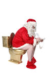 Santa sitting on golden toilet Stock Photo
