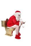 Santa sitting on golden toilet. Writing his Christmas list stock photo
