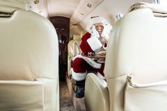 Santa Sitting In Private Jet. Bored Santa Claus sitting in private jet Royalty Free Stock Photography