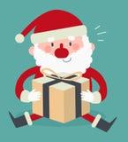 Santa Sitting sveglia e tenere un presente Fotografie Stock Libere da Diritti